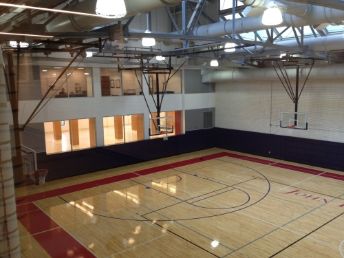 The basketball coaches offices have glass windows overlooking the court.